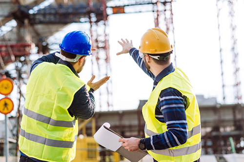 engineer, construction site manager discuss project