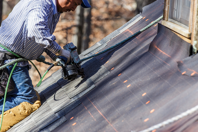 Roofer nailing shingles